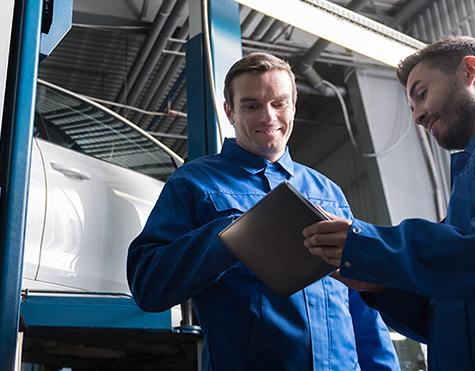 Mechanics both checking an inspection sheet - MOT Slough